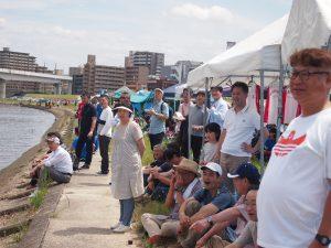 川岸で応援する社員たち